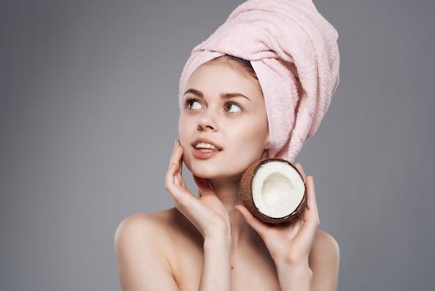 Kobieta z ręcznikiem na głowie z egzotycznymi owocami w ręku przycięty widok
