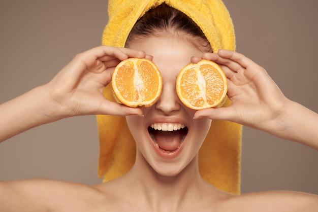 Kobieta z ręcznikiem na głowie z owocową mandarynką w ręku przycięty widok