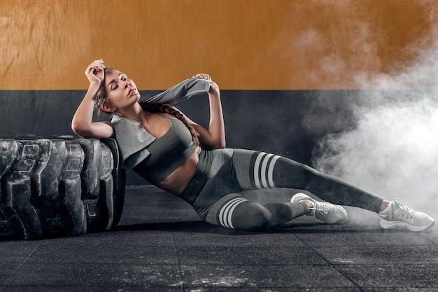 Kobieta z ręcznikiem na ramionach odpoczywa po treningu