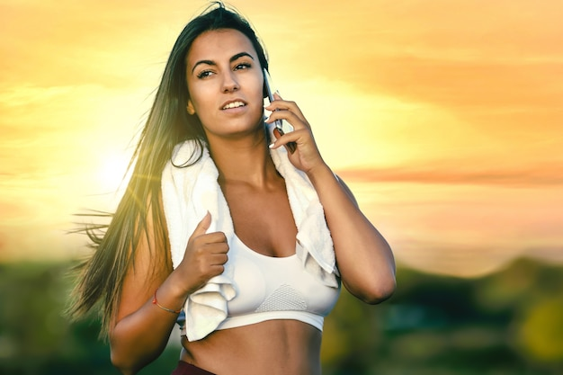 Kobieta z ręcznikiem na szyi rozmawia przez telefon po ćwiczeniach o zachodzie słońca