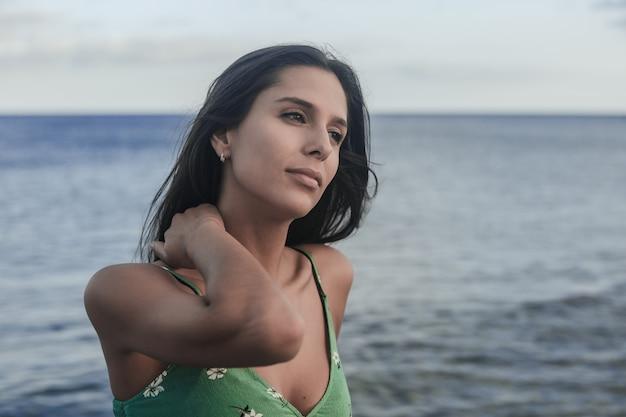 Kobieta z ręką na szyi, kontemplując morze