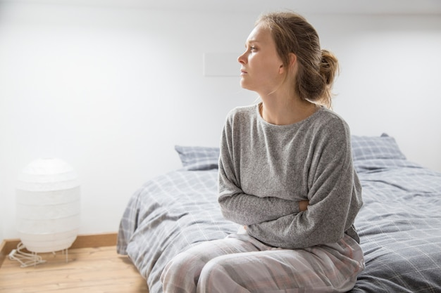 Kobieta z rękami na brzuchu cierpi na ból, patrząc na bok