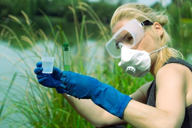 Kobieta z rękami w rękawiczkach trzyma szklankę z próbką wody. pobieranie próbek z wody otwartej.