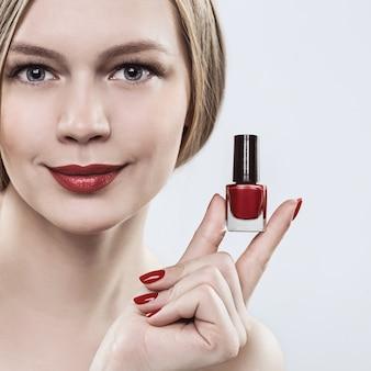 Kobieta z rękami z butelką czerwonego lakieru do paznokci, czerwoną szminką na ustach i czerwonymi paznokciami.