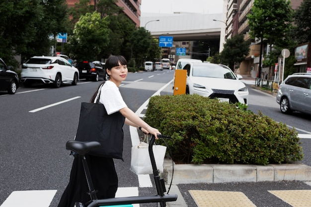 Kobieta z rowerem elektrycznym w mieście