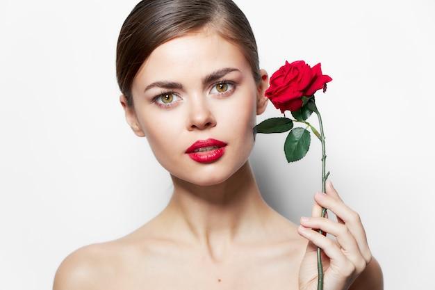 Kobieta z różą czerwone usta obnażone ramiona czarują jasny makijaż