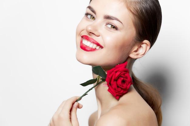 Kobieta z różą czerwone usta z szerokim uśmiechem czarują nagie ramiona