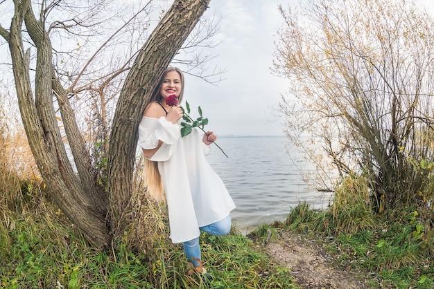Kobieta z różą pozowanie przed wodą jeziora