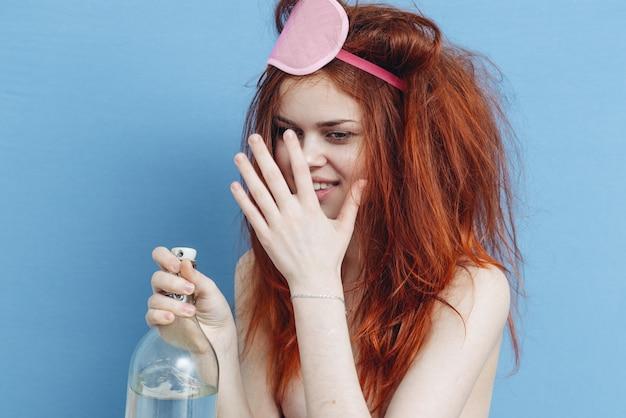 Kobieta z rozczochraną maską do włosów czerwona butelka alkoholu niebieskie tło