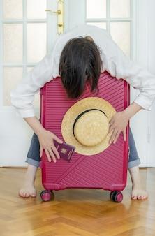 Kobieta z różową walizką trzyma letni kapelusz i rumuński paszport oraz gotową podróż.