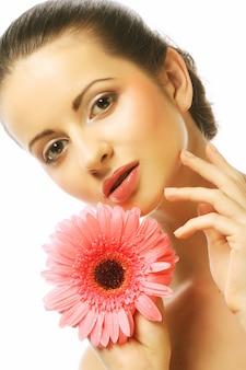 Kobieta z różowym gerber kwiatem odizolowywającym na bielu