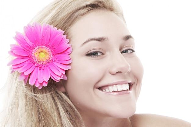 Kobieta z różowym kwiatem w jej włosach