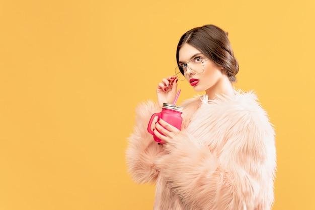 Kobieta z różowym pije słojem na kolorze żółtym
