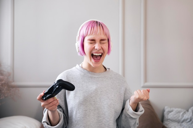 Kobieta z różowymi włosami grająca w grę wideo