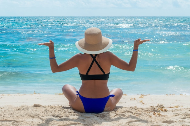 Kobieta z rozpostartymi ramionami otrzymująca energię ze słońca siedząc na piasku twarzą do morza. kobieta w kapeluszu słońca. koncepcja wakacje. wiosna w cancun, meksyk.
