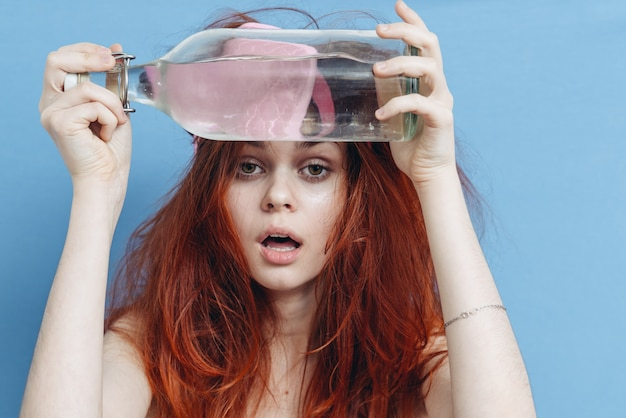 Kobieta z rudymi włosami butelka alkoholu kaca maska snu niebieskie tło. wysokiej jakości zdjęcie