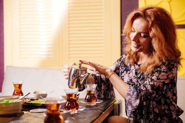 Kobieta z rudymi włosami nalewa czarną herbatę ze stalowego dzbanka do szklanki armudu