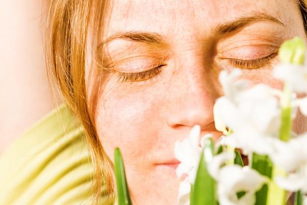 Kobieta z rudymi włosami, piegami i bukietem białych kwiatów