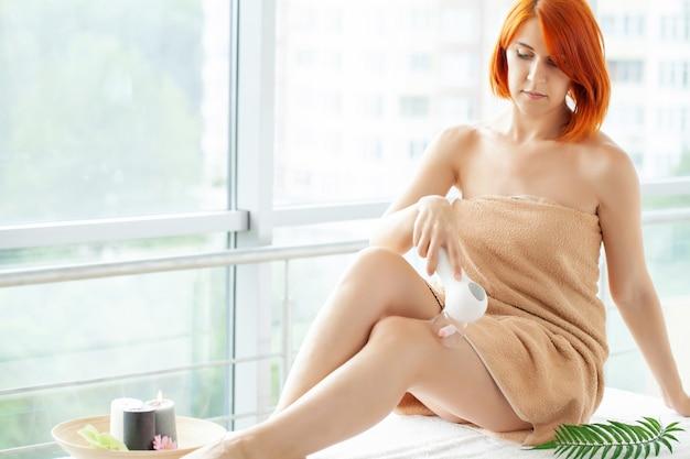 Kobieta z rudymi włosami robi masaż lpg w domu w mieszkaniu z panoramicznymi oknami