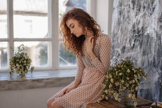 Kobieta z rudymi włosami siedzi na tle okna,