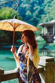 Kobieta z rudymi włosami trzyma w ręku parasol na tle jeziora