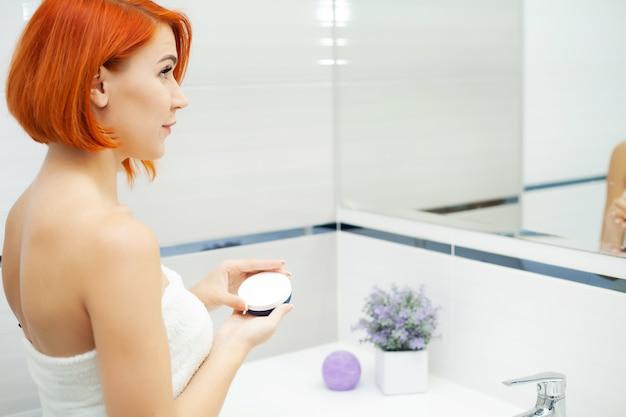 Kobieta z rudymi włosami w łazience używać produktów do pielęgnacji