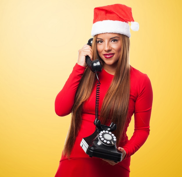 Kobieta z santa kapelusz zabawy podczas rozmowy na telefon