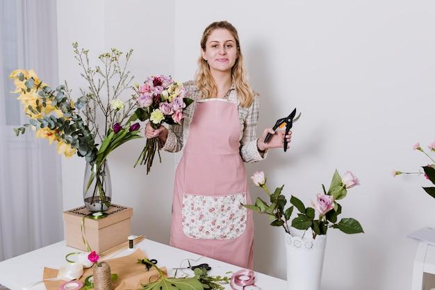 Kobieta z sekatorem i różnymi kwiatami
