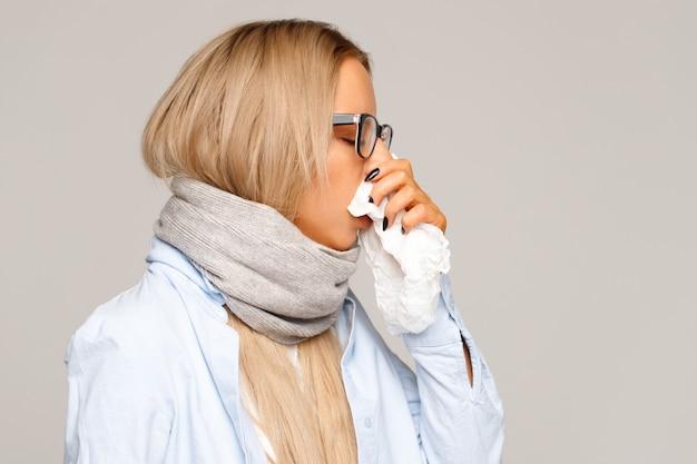 Kobieta z serwetka dmuchanie nosa, alergiczny nieżyt nosa