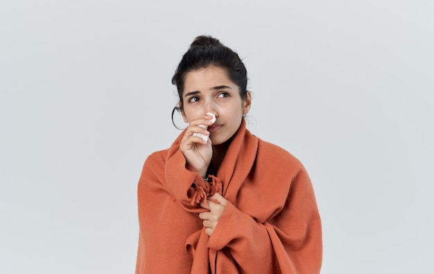 Kobieta z serwetką jest owinięta w pomarańczową kratę na lekkich kosmicznych problemach zdrowotnych.