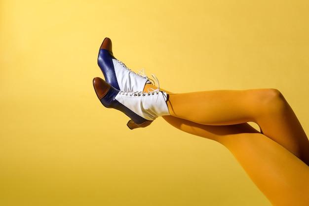 Kobieta z sexy nogi na sobie tritone retro skórzane buty i musztardowe kolorowe collants