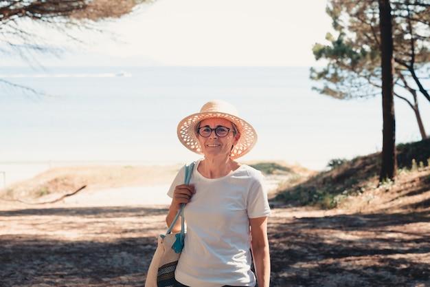 Kobieta z siwymi włosami na plaży w super słoneczny dzień senior wolność koncepcja kopia przestrzeń słońce