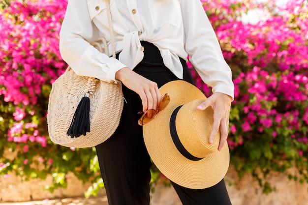 Kobieta z słomianym kapeluszem pozuje nad różowym kwitnącym drzewem w pogodnym wiosna dniu