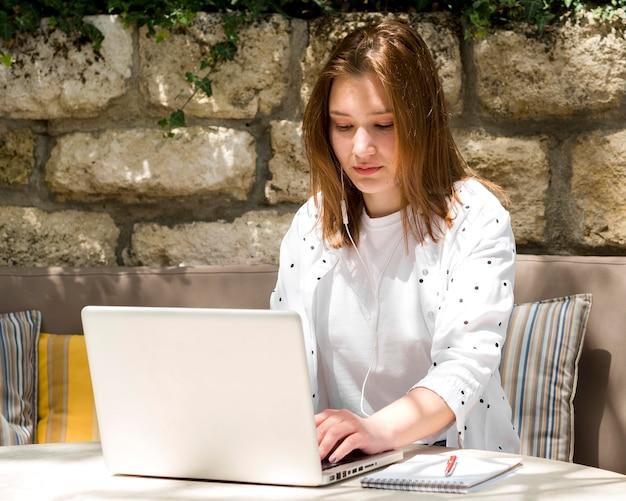 Kobieta z słuchawkami pracuje na laptopie outside