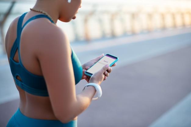 Kobieta z smartphone. ciemnoskóra kobieta trzyma smartfon podczas wyszukiwania muzyki do ćwiczeń