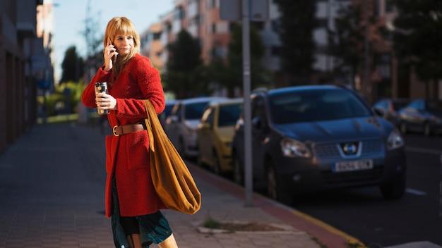 Kobieta z smartphone i napoju na ulicie