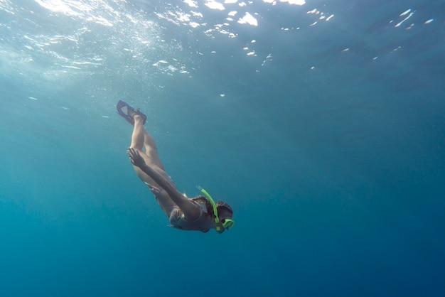 Kobieta z sprzęt do nurkowania pływanie w oceanie