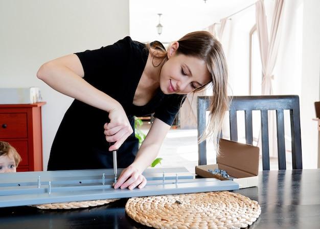 Kobieta z śrubokrętem instalująca meble w domu osobiście