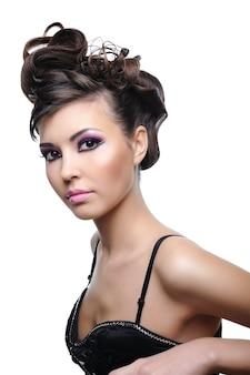 Kobieta z stylową fryzurą mody i jaskrawym fioletowym makijażem