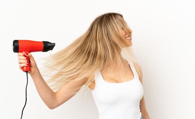 Kobieta z suszarką do włosów na białym tle