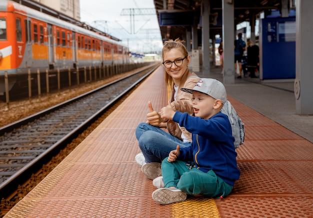 Kobieta z synem na peronie w pobliżu pociągu. dziewczyna z chłopcem w wieku przedszkolnym siedzi na stacji kolejowej w pobliżu pociągu. podróżuj koleją. matka i syn czekają na pociąg. rodzinna wycieczka. bydgoszcz.