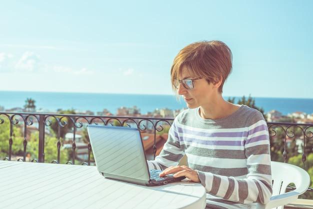 Kobieta z szkłami i przypadkowymi płótnami pracuje przy laptopem outdoors na tarasie