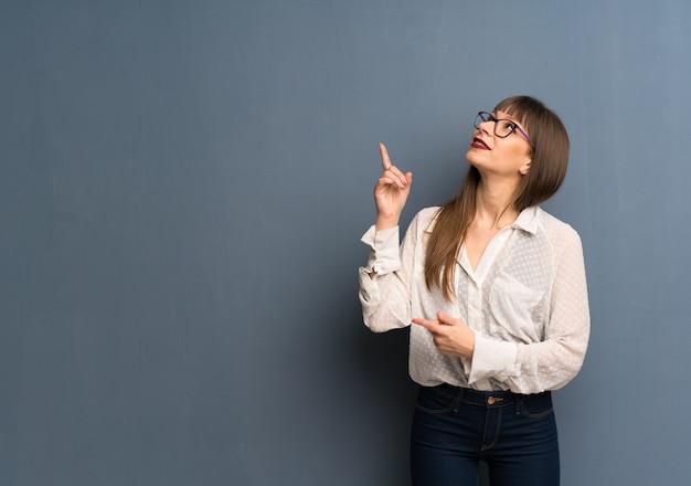 Kobieta z szkłami nad błękitną ścianą wskazuje doskonałego pomysł i przyglądającego up