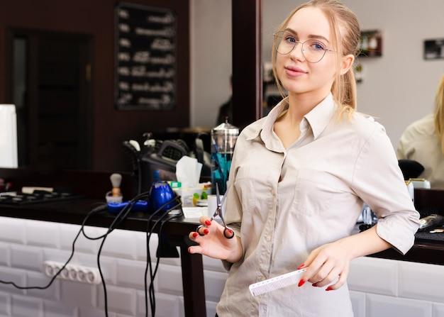 Kobieta z szkłami pracuje przy fryzjera męskiego sklepem