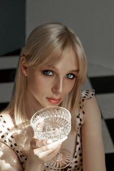 Kobieta z szklanym alkoholem w dłoni siedzi na podłodze, stare wnętrze, romantyczny wygląd blond dziewczyna. cień okna na ciele kobiety, alkoholizm