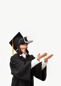 Kobieta z szlafrokiem i czapką ukończenia szkoły na sobie zestaw wirtualnej rzeczywistości