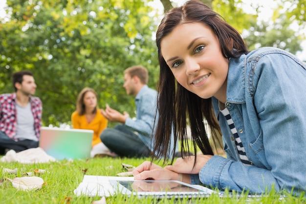 Kobieta z tablet pc, podczas gdy inni za pomocą laptopa w parku