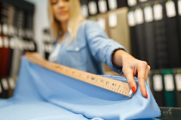 Kobieta z taśmą mierzy zbliżenie tkaniny w sklepie tekstylnym. półka z materiałem do szycia