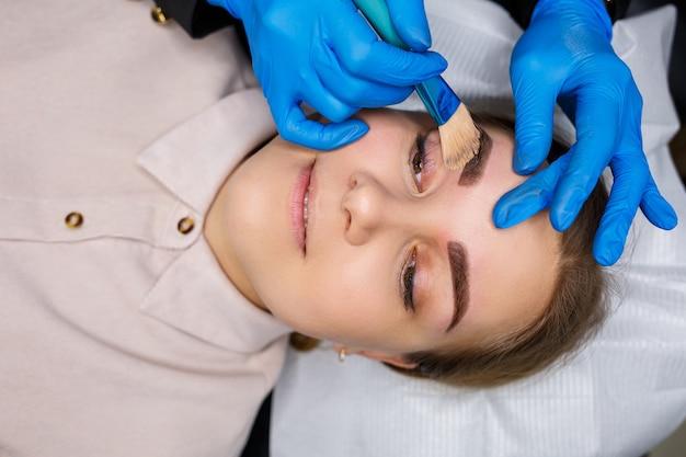 Kobieta z tatuażem do makijażu permanentnego na brwiach. kosmetyczka z bliska sprawia, że makijaż nakłada podkład. profesjonalny makijaż i pielęgnacja kosmetyczna skóry.