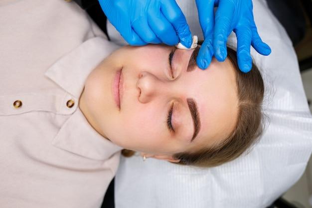 Kobieta z tatuażem do makijażu permanentnego na brwiach. kosmetyczka z bliska wykonuje szkic brwi. profesjonalny makijaż i pielęgnacja kosmetyczna skóry.
